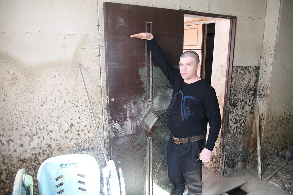 Илья Ларионов показывает какой был уровень воды вовремя наводнения. Фото: Анна Васильева