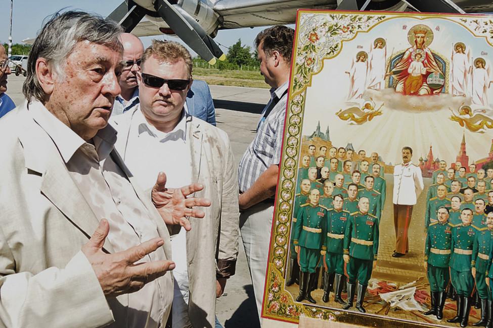 Писатель Александр Проханов рядом сиконой, накоторой изображен Иосиф Сталин. Фото: saratovnews.ru