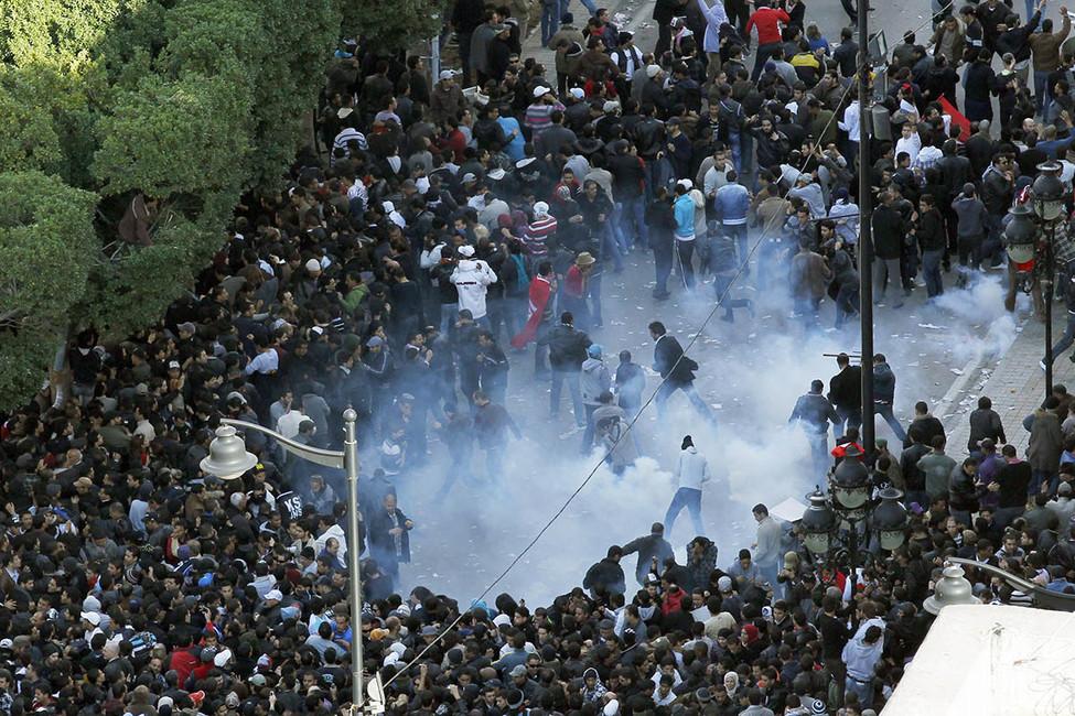 Столкновение полиции ипротестующих вТунисе, январь 2011года. Фото: Christophe Ena/ AP