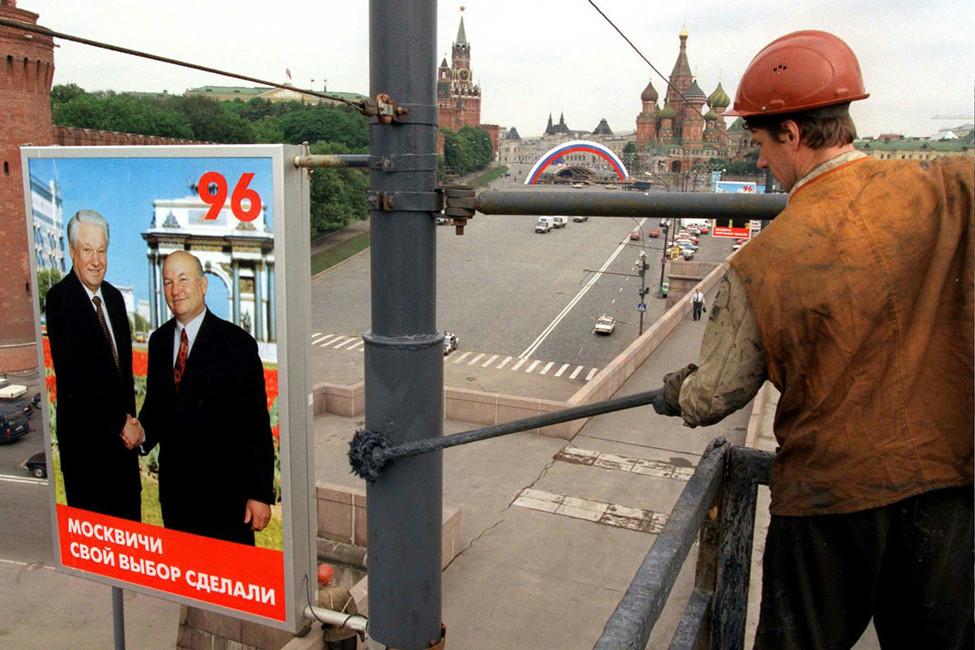 Рабочий красит столб, накотором висит агитационный плакат спрезидентом России Борисом Ельциным имэром Москвы Юрием Лужковым. Москва, 1996год. Фото: Reuters