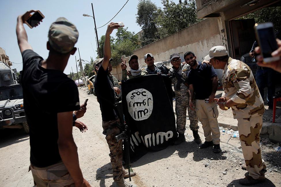 Члены 9-й бронетанковой дивизии Иракской армии фотографируются сфлагом исламского государства, Мосул, Ирак, 17июня 2017года. Фото: Alkis Konstantinidis/ Reuters