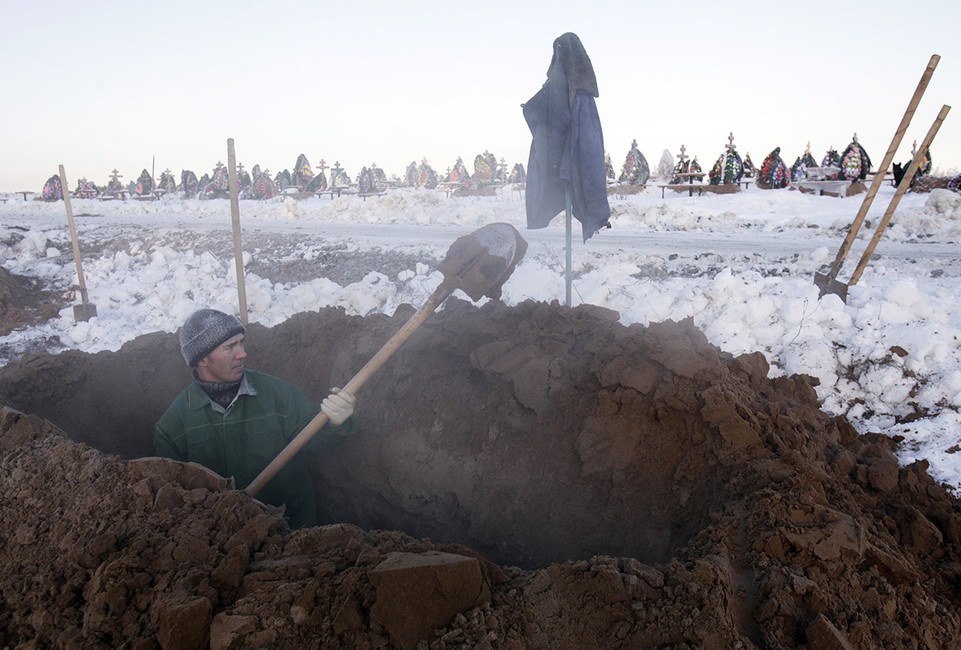 Рабочий копает могилу накладбище. Фото: Денис Синяков/ Reuters