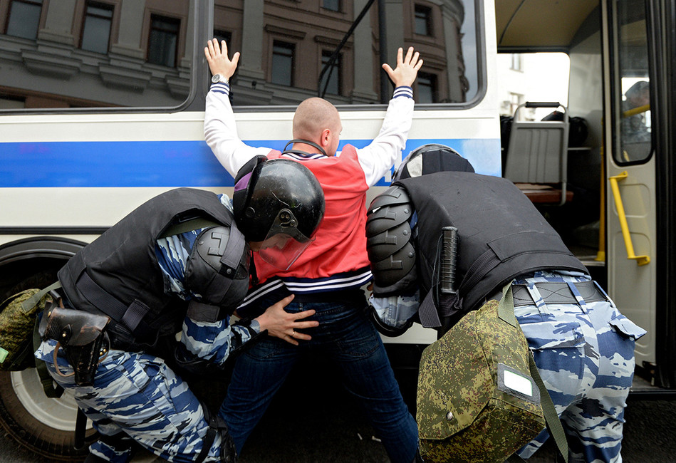 Сотрудники полиции вовремя задержания участника митинга. Фото: Максим Поляков/ Коммерсантъ