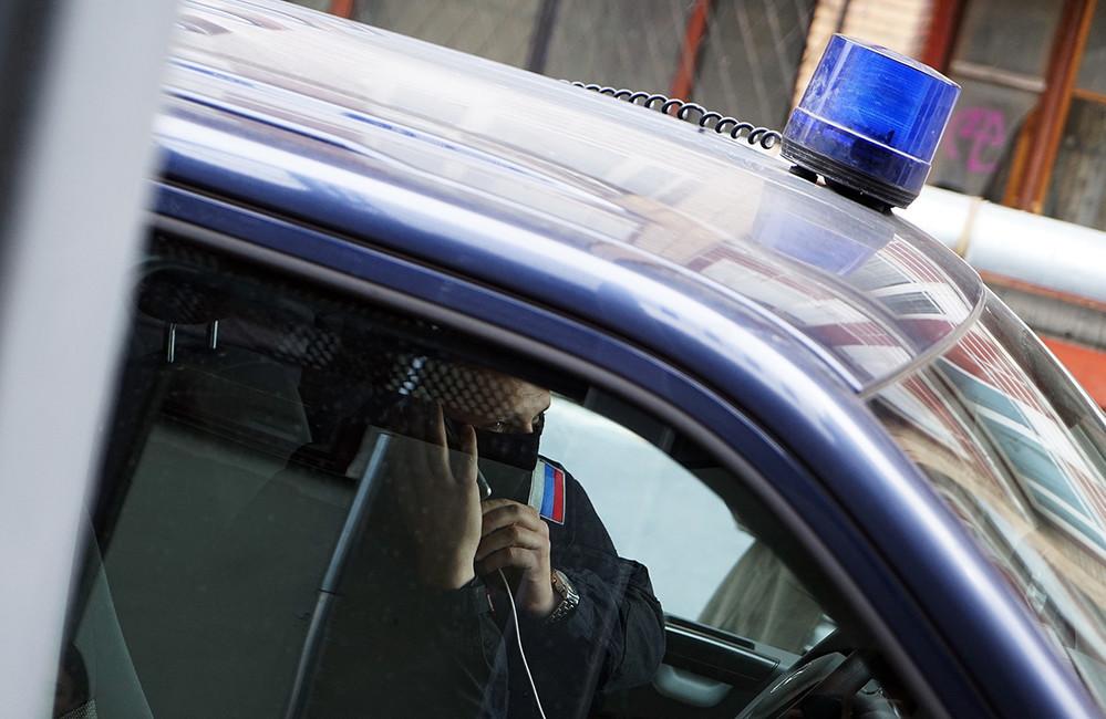 Обыски втеатре «Гоголь-Центр». Сотрудник правоохранительных органов вкабине полицейского автомобиля вовремя разговора потелефону. Фото: Алексей Абанин/ Коммерсантъ