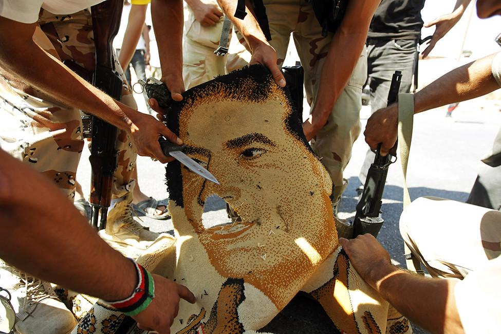 Ливийские революционеры рвут ковер сизображением Муамара Кадаффи, 2011год. Фото: Zohra Bensemra/ Reuters