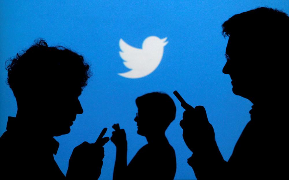 Люди нафоне логотипа Twitter. Фото: Kacper Pempel/ Reuters